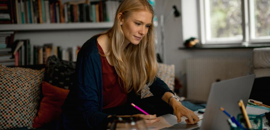 A photo of a female using a laptop and holding a pink pencil.