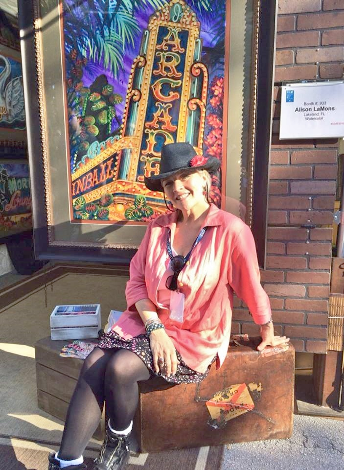 Alison LaMons sits in front of a sample of her art.