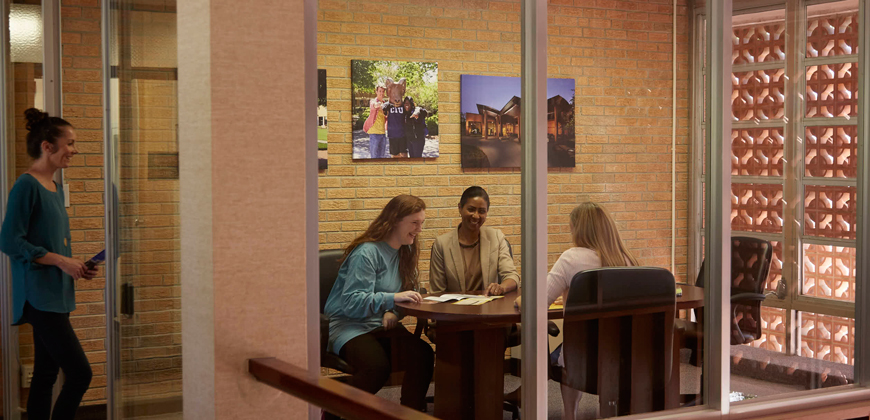 CIU financial aid and admissions counselors assisting a student.