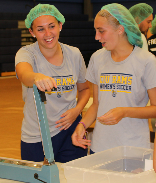 Women's soccer players Meghan Esquinaldo (left) and Taylor Endicott share a laugh as they wait to seal another bag of lentil casserole.