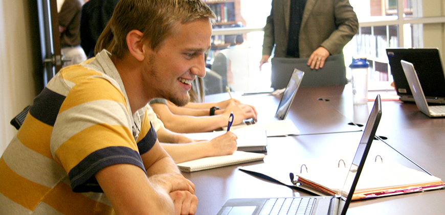 A photo of a CIU student in class using a laptop.