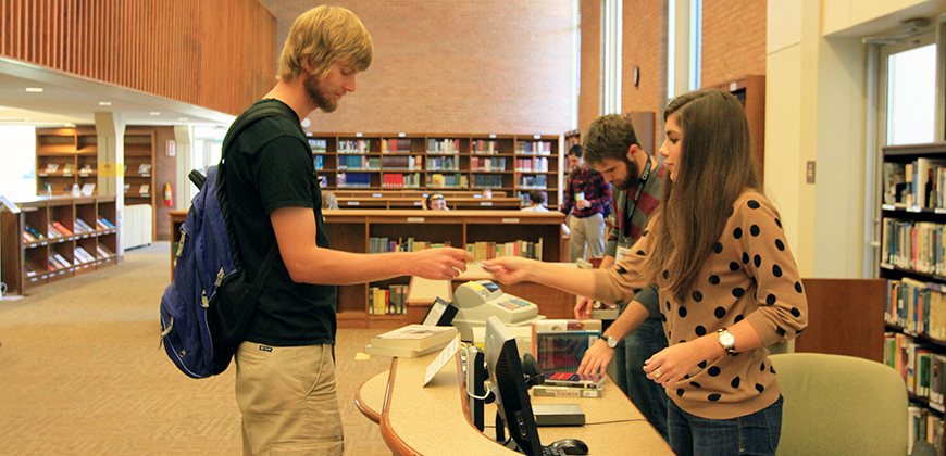 A photo of a student worker assisting a student in the library at Columbia International University.