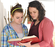 A photo of Sara Nixon, a CIU alumnus, assisting a student.