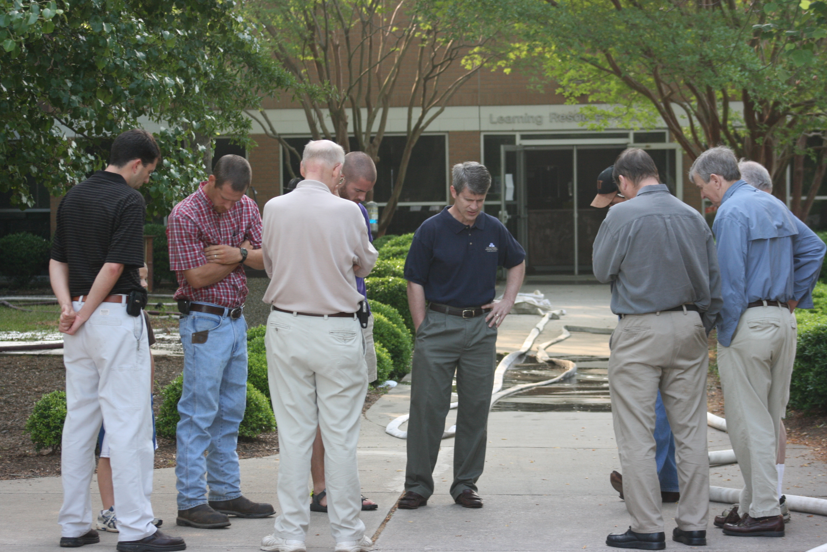 CIU President Bill Jones (center) leads staff members in prayer outside of the l