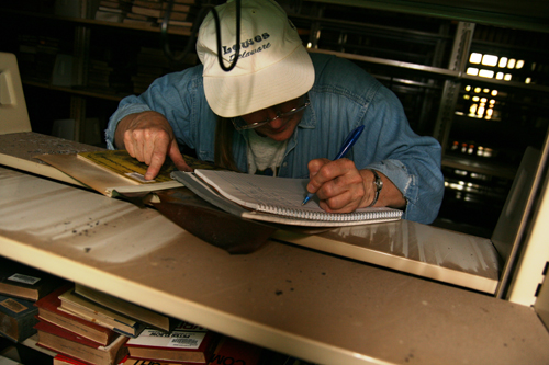 A worker catalogs the number of a book that was partially damaged by the fire.