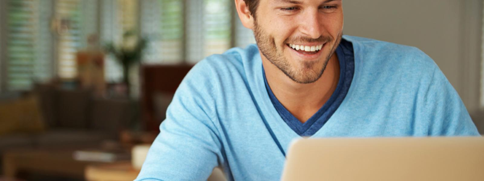 A happy online student using a laptop in a home environment.
