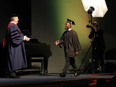 Justin Belk being congratulated by CIU President Dr. Mark Smith.