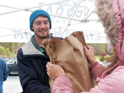 Chandler Sims offers a smile and a bag of groceries to a local resident.