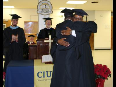 A graduate of the CIU Prison Initiative receives his diploma and hugs Initiative Director Andre Melvin.