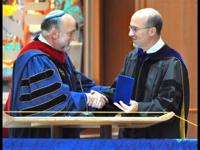 CIU professor Dr. Bryan Beyer (right) receives congratulations from Rabbi David