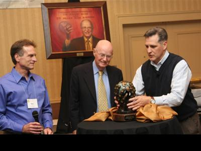 Robertson McQuilkin (center) is honored by Marv Newell of CrossGlobal Link (left