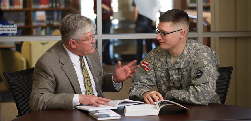 A seminary professor speaking with a military chaplaincy student in an office environment.