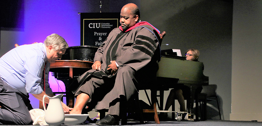 CIU President Dr. Mark Smith washes the feet of CIU Professor Dr. Andre Rogers at CIU's 2019 Convocation