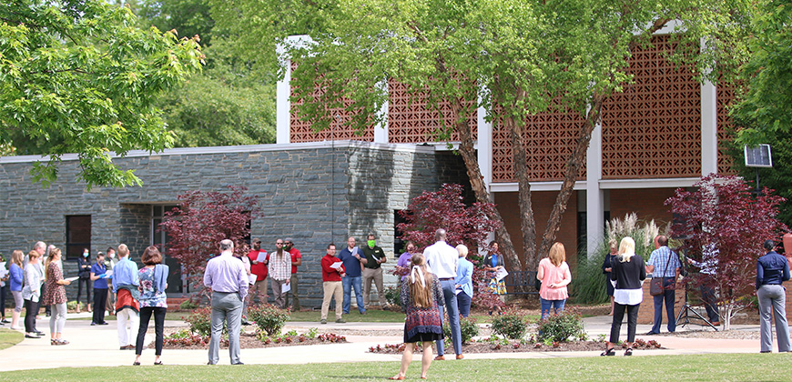 CIU staff members maintain social distancing in the CIU Quad as they join in a hymn sing.