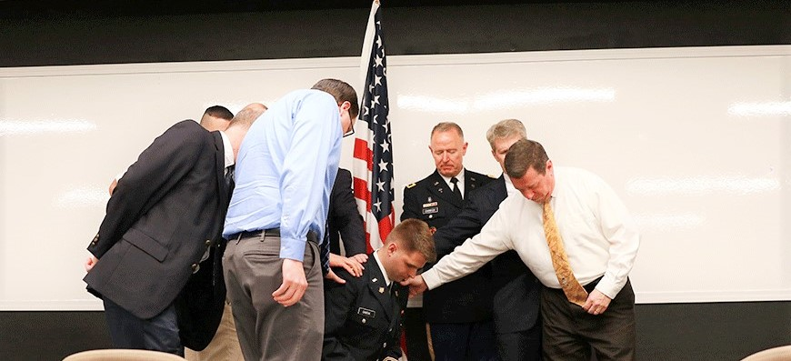 ohn Dabeck is commissioned for military chaplaincy during a ceremony at CIU. Among those praying for him are Dean of Students Rick Swift, Chancellor Bill Jones and his father Larry Dabeck (in uniform).