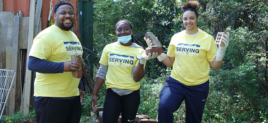 CIU Head Basketball Coach Danielle Fleming (right) is joined by Assistant Coach Daron Fleming and junior Britney Brown as they clean up EZE Farms, a ministry to inner city youth.
