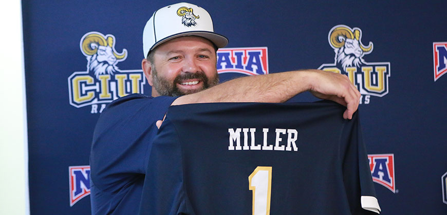 Head Baseball Coach Jonathan Johnson presents Dr. Johnny Miller with this own CIU Rams jersey.