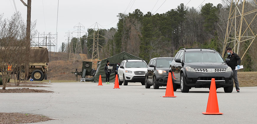 Community members line up in a CIU parking lot to receive the COVID-19 vaccination.
