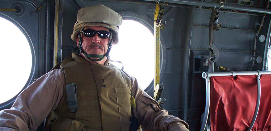 Dr. Mike Langston as a U.S. Navy chaplain in a helicopter over Afghanistan.