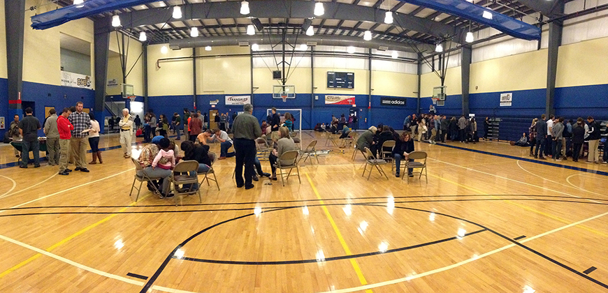 A photo of students, faculty and staff praying in the gym during Prayer Day at CIU.