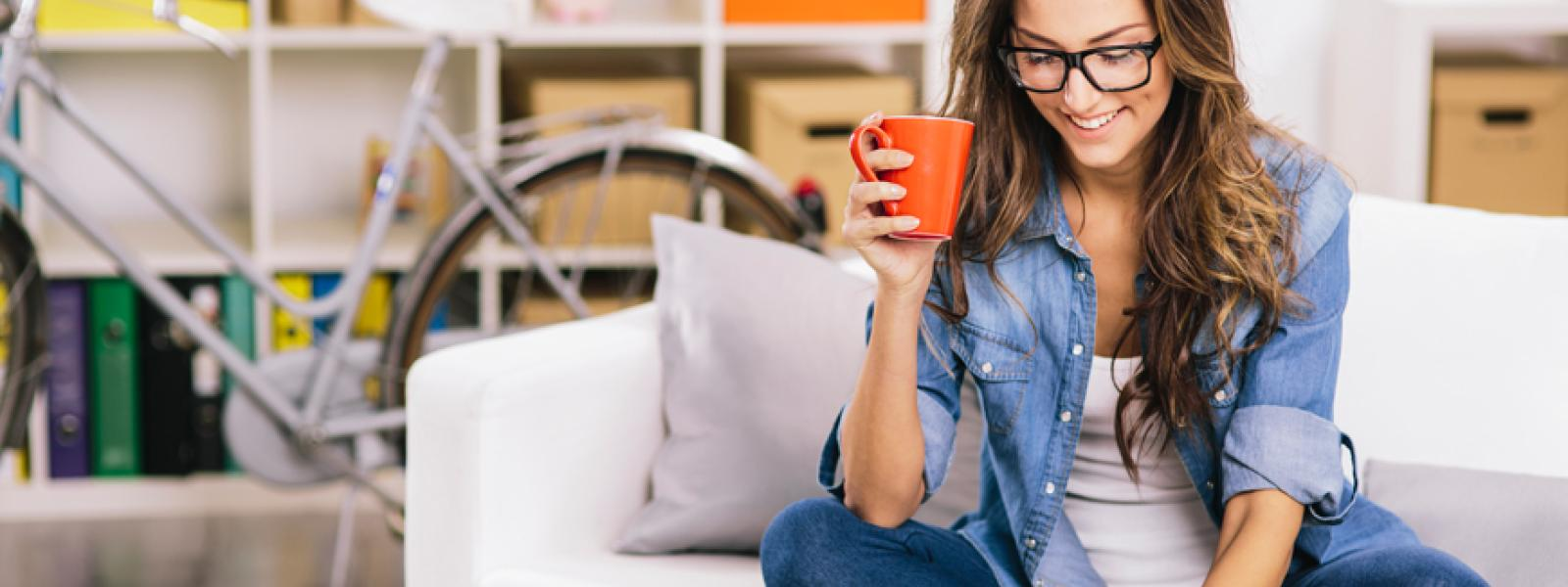 A photo of an online student wearing a denim shirt and holding an orange coffee cup.