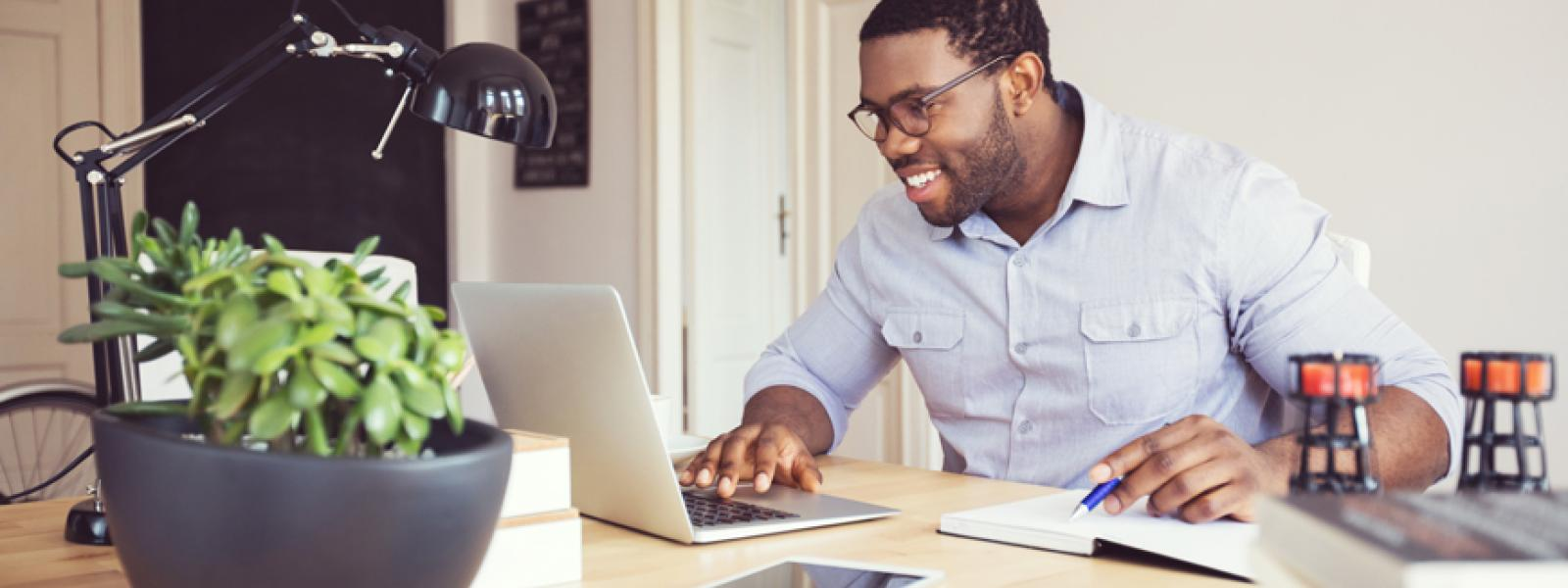 Photo of an online student using a laptop in a home or casual office environment.