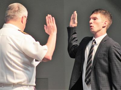 Caleb McKillop takes the oath with the assistance of CIU Professor Dr. Mike Langston, a former Navy chaplain.