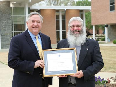 Dr. John Crutchfield (right) is presented with the Excellence In Teaching award by CIU president Dr. Mark Smith.