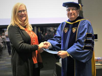 Patricia England receiving her Diploma in Women's Leadership from Provost Dr. James Lanpher