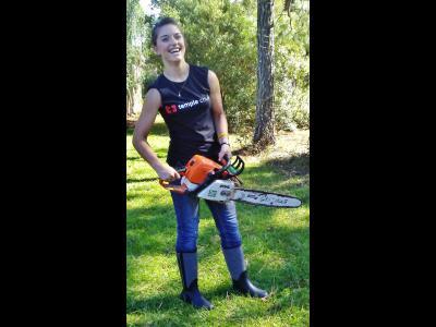 CIU student Heather Blackburn assists with a chainsaw.