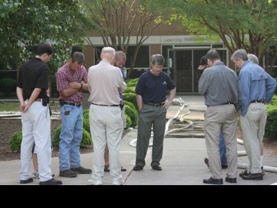 CIU President Bill Jones (center) leads staff members in prayer outside of the l